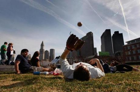 Jonathan Fisher, 24, foreground, tossed a ball while relaxing during a Spring day on the Greenway.